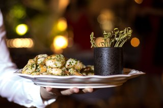 server-holding-platter-of-garlic-herb-shrimp-on-plate-toothpicks-wedding-food-ideas-hors-doeuvres