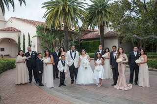 bride-and-groom-with-bridesmaids-in-tan-taupe-gowns-groomsmen-in-tuxedos-groom-in-white-tuxedo-jacke