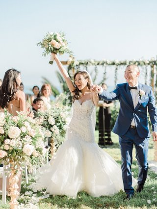wedding-ceremony-exit-bride-groom-recessional-hands-in-air-bouquet-flowers-muted-color-palette