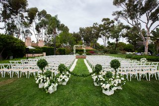 wedding ceremony on lawn outdoor hotel wedding white flowers greenery garden setting