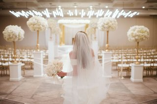 wedding ceremony white and gold decor bride with bouquet heatherlily looking at room
