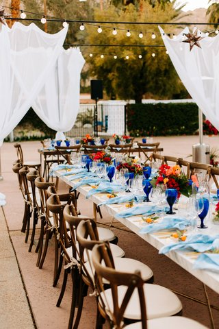 wedding reception long marble table wood chairs light blue napkins royal blue goblets bistro lights