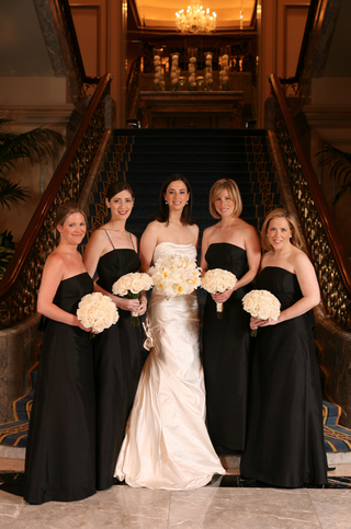bride-in-a-ruched-strapless-dress-with-bridesmaids-in-long-black-dresses