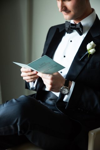 groom in tuxedo in suite reading card from bride love laughter and happily ever after