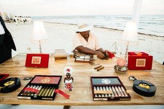 a-gentleman-rolls-cigars-at-a-beach-wedding-in-playa-del-carmen-mexico