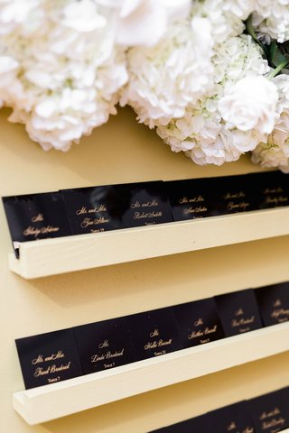 wedding-reception-escort-card-glossy-black-paper-with-gold-calligraphy-on-floating-shelf-flowers