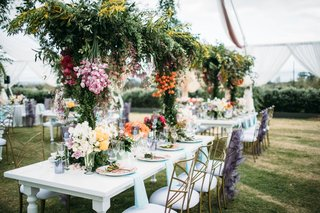 wedding reception white table suspended greenery centerpiece with pink orange flowers gold chairs