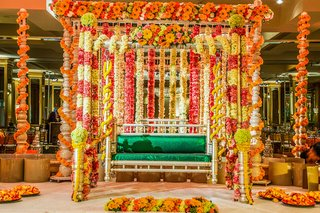 tall-gold-structure-wrapped-with-garlands-of-flowers