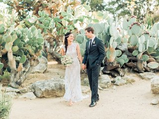 boho-chic-bride-and-groom-walk-hand-in-hand-bride-with-jeweled-headband-desert-wedding