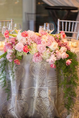 cascading-floral-arrangement-blush-ivory-peonies-low-green-leaves-linen-overlay-lace