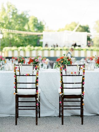 bride-and-groom-wedding-chairs-with-pom-pom-garland-decorations