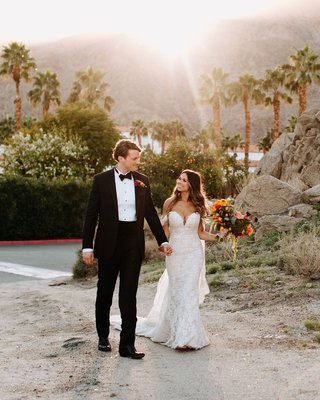 bride in off shoulder lace wedding dress with groom in tuxedo la quinta resort and club colorful flowers