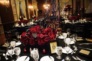 wedding-reception-table-with-a-red-rose-and-manzanita-branch-centerpiece