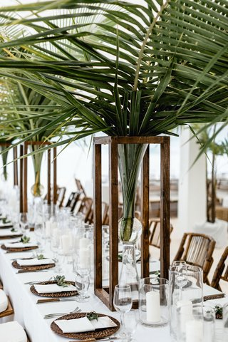 wedding-reception-on-beach-long-table-palm-leaf-centerpieces-wood-rattan-tropical-decor-neutral