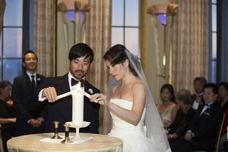 bride-and-groom-at-wedding-lighting-pillar-candle