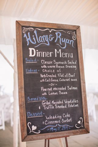 the-menu-is-printed-in-blue-and-white-lettering-on-a-chalkboard
