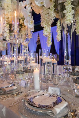 wedding-reception-tall-centerpiece-white-orchids-floating-candles-silver-plates-chargers