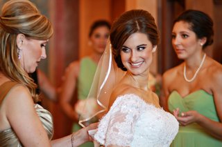 mother-of-the-bride-buttoning-her-daughters-gown