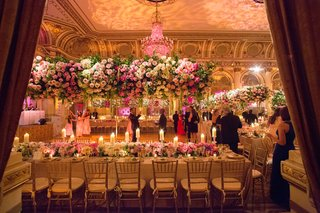 wedding-reception-with-long-table-low-runner-of-flowers-with-candles-and-tall-centerpieces-pink