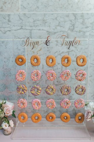 colorful-donut-wall-on-acrylic-stand-at-wedding-reception