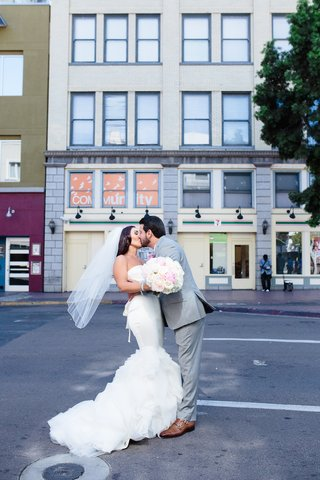 bride-in-a-strapless-vera-wang-dress-with-ruffled-skirt-veil-kisses-groom-in-grey-suit-on-street