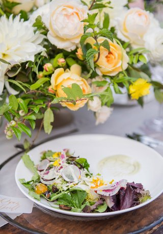 wedding-reception-wood-table-clear-charger-plate-white-salad-plate-fresh-greenery-radish-tomato