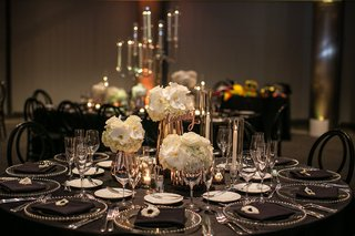 three-small-floral-arrangements-as-centerpiece-on-wedding-reception-table-with-black-linens