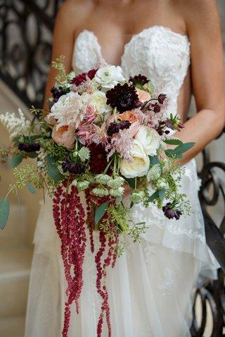 bride-holding-fall-bouquet-burgundy-amaranthus-white-flowers-pink-ranunculus-rose-eucalyptus