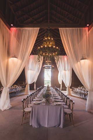 rustic-wedding-reception-in-vintage-barn-lavender-linens-wood-chairs-chandeliers-greenery-drapery