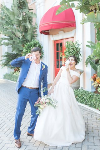 the-confused-millennial-off-shoulder-gown-and-groom-in-navy-play-with-cameras-at-wedding-shoot