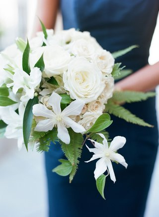 bridesmaids-wearing-navy-blue-dresses-holding-bouquets-of-roses-greenery-and-ferns-fern