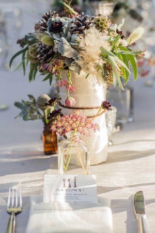 wildflower-and-pinecone-centerpieces-wrapped-on-book-pages-tied-in-twine