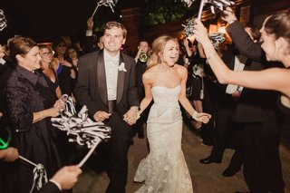 bride-in-mira-zwillinger-wedding-dress-groom-in-tux-grand-exit-with-black-and-white-pom-poms