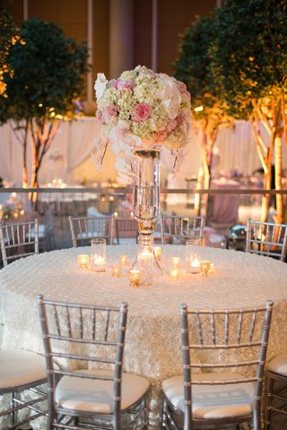 round-table-white-linen-small-candles-clear-case-white-pink-flowers-hanging-down-gray-chairs