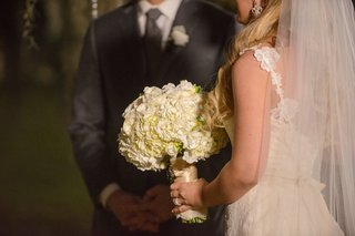 bride-in-white-wedding-dress-holds-ivory-hydrangea-bouquet