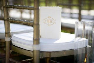 wedding-ceremony-program-gold-monogram-booklet-on-white-chair-cushion-gold-chair