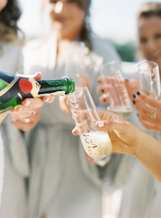moet-and-chandon-champagne-being-poured-for-bridesmaids-in-robes-personalized-champagne-flutes