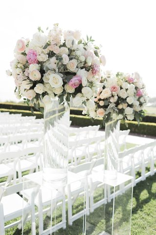 wedding-ceremony-grass-lawn-white-chairs-acrylic-lucite-riser-tall-flower-arrangements