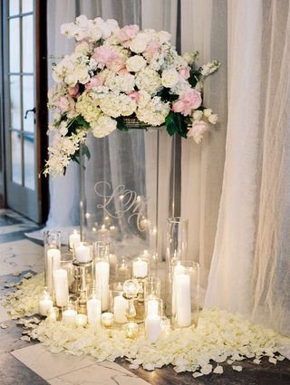 wedding-ceremony-grouping-of-candles-around-clear-riser-with-white-and-pink-flowers-on-top-flowers