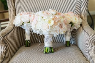 white-and-light-pink-rose-bouquets-for-bride-and-bridesmaids-on-arm-chair-with-crystal-wraps