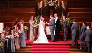 wedding-ceremony-bride-and-groom-at-front-of-church-red-carpet-wood-stairs-beaded-bridesmaid-gowns