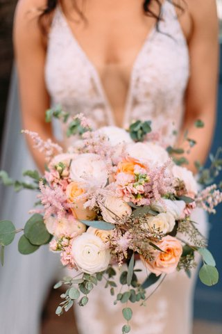 bride-with-plunging-neckline-holding-bouquet-pastel-pink-and-orange-pink-white-ranunculus-rose