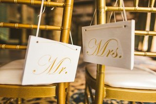 wedding-reception-decoration-gold-chair-white-cushion-white-gold-calligraphy-rectangle-sign-ribbon