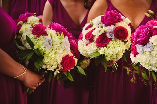 bridesmaids-in-magenta-bridesmaid-dresses-holding-bouquets-ivory-hydrangeas-and-pink-rose-peonies