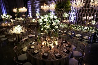dark-lighting-at-wedding-reception-white-roses-and-greenery-in-tall-centerpiece