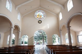 white-interior-stained-glass-window-wood-benches-at-nuestra-senora-de-guadalupe-playa-del-carmen