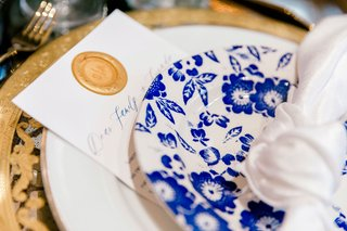 wax-seal-on-on-note-to-guests-under-blue-and-white-plate-gold-charger-plate
