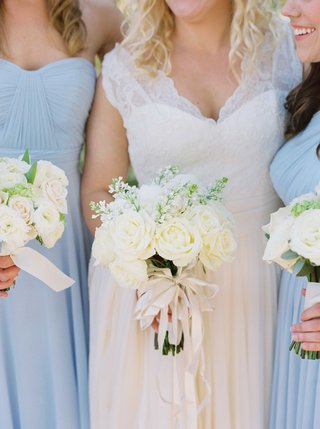 bride-in-white-lace-dress-bridesmaids-in-light-blue-gowns-white-rose-bouquet-ivory-ribbon