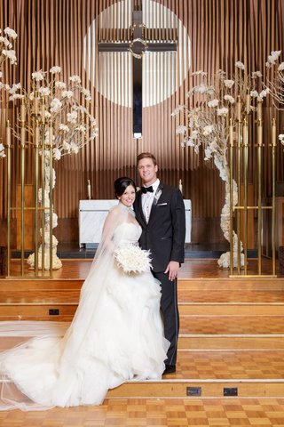 bride-in-lazaro-ball-gown-with-tulle-cape-groom-in-tuxedo-in-front-of-christian-altar