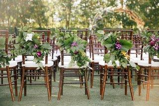 wedding-ceremony-dark-wood-chairs-white-cushions-green-leaves-greenery-purple-yellow-flowers